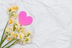 Vårpåskliljabouqet på den vita hantverkpappersbakgrunden och Royaltyfri Fotografi