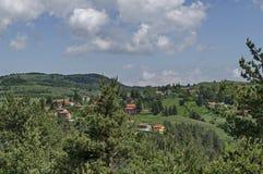 Vårplats med berggläntan, skogen och det bostads- området av den bulgarian byn Plana, Plana berg Arkivfoton