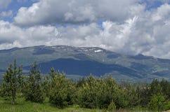 Vårplats med berggläntan, skogen och det bostads- området av den bulgarian byn Plana, Plana berg Arkivfoto