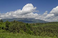Vårplats med berggläntan, skogen och det bostads- området av den bulgarian byn Plana, Plana berg Royaltyfri Fotografi