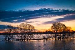 Vårsolnedgång på floden Arkivbild
