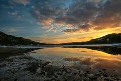 Vårsolnedgång på sjön Arkivfoto