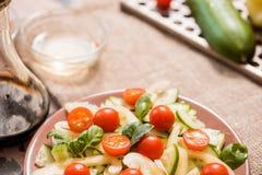 Vårsommar bantar sallad med jordgubbar, gurkan, grön fältsallad och yoghurtmintkaramellsås som tjänas som i blåttplatta med torkd Royaltyfri Bild