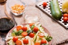 Vårsommar bantar sallad med jordgubbar, gurkan, grön fältsallad och yoghurtmintkaramellsås som tjänas som i blåttplatta med torkd Royaltyfri Foto