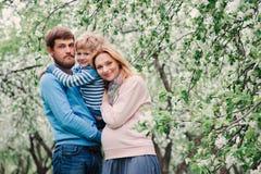 Vårstående av den lyckliga familjen som tycker om ferier i blommande trädgård royaltyfri fotografi