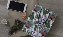 Vårutrymme med telefonen, blommor och packen royaltyfri bild