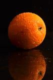 Våt apelsin på en svart bakgrund Fotografering för Bildbyråer