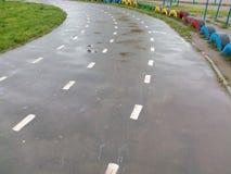Våt asfalt som joggar vägen, vänder till det vänstert på skolastadion Fotografering för Bildbyråer