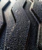 Våt bakgrund för gummihjuldäckmönstertextur arkivfoto