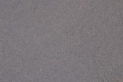 Våt grå färgasfalt under ett tunt lager av vatten textur Royaltyfri Bild