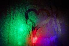 våt hjärta för tecknat exponeringsglas Ljusen av nattstaden till och med det våta exponeringsglaset arkivbilder