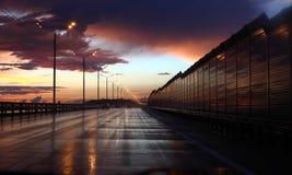 Våt huvudväg på natten Arkivbild