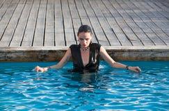Våt kvinna i svart klänning i en simbassäng Arkivbilder
