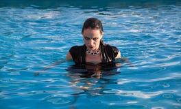 Våt kvinna i svart klänning i en simbassäng Royaltyfria Bilder