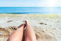 Våt kvinnligfot på stranden och sanden Arkivbilder