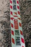 Våt målarfärg för varning på ett plast- band på grov asfaltbeläggning Arkivbilder