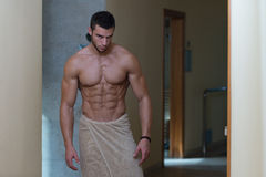 Våt muskulös sexig man som slås in i handduk arkivbild
