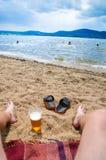 Våt pojkes fot på stranden och sand med koppen av öl Royaltyfri Fotografi