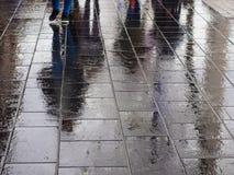 Våt trottoar i dozhdlivy dag med reflexion av gångare Royaltyfri Bild