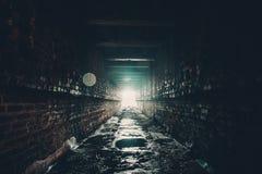 Våt tunnel för mörk tegelsten eller övergiven underjordisk industriell korridor med ljus slutligen Royaltyfri Foto