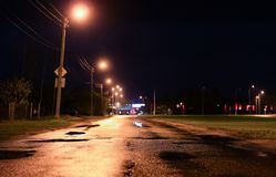 Våt väg för natt, vattenpölar arkivfoton