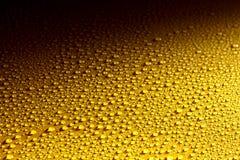 Våt yttersida för gul metall med att glittra droppar Fotografering för Bildbyråer