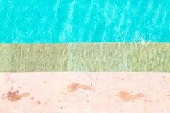 Våta fottryck på sida av simbassängen arkivfoton