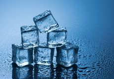 Våta iskuber på blå bakgrund Arkivbild