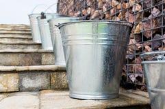 Våta metallhinkar på trappa Arkivbilder