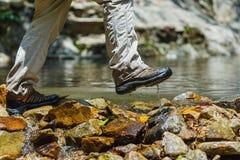 Våta skor som fotvandrar lopplivsstilbegrepp, äventyrar, korsar strömmen Royaltyfria Bilder