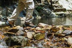 Våta skor som fotvandrar lopplivsstilbegrepp, äventyrar, korsar strömmen Fotografering för Bildbyråer