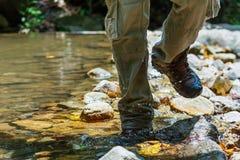 Våta skor som fotvandrar lopplivsstilbegrepp, äventyrar, korsar strömmen Royaltyfri Foto