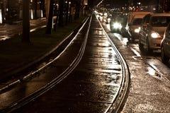 Våta spårvagnrailes i ljuset och gatorna Arkivbilder