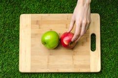Végétariens et cuisson sur la nature du thème : main humaine tenant les pommes rouges et vertes sur le fond d'une planche à décou Images libres de droits