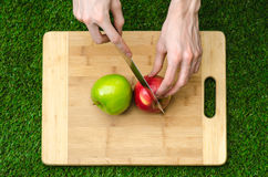 Végétariens et cuisson sur la nature du thème : main humaine tenant les pommes rouges et vertes sur le fond d'une planche à décou Photos libres de droits
