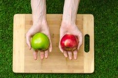 Végétariens et cuisson sur la nature du thème : main humaine tenant les pommes rouges et vertes sur le fond d'une planche à décou Image libre de droits