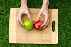 Végétariens et cuisson sur la nature du thème : main humaine tenant les pommes rouges et vertes sur le fond d'une planche à décou Photos stock