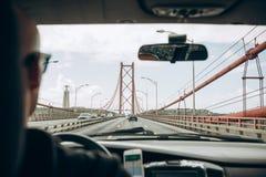 véhicule à l'intérieur de vue Le conducteur conduit par le pont appelé le 25 avril à Lisbonne au Portugal Voyage par la voiture o Photographie stock