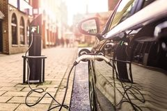 Véhicule électrique chargeant sur la rue, au R-U image libre de droits