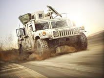 Véhicule blindé militaire se déplaçant à un haut débit de vitesse avec la tache floue de mouvement au-dessus du sable générique illustration stock
