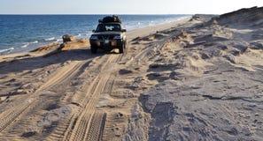 Véhicule d'entraînement à quatre roues sur une plage lointaine Images libres de droits
