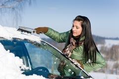 Véhicule de l'hiver - la femme enlèvent la neige du pare-brise photo libre de droits