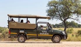 Véhicule de safari avec des touristes recherchant des animaux photographie stock libre de droits