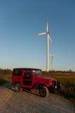 Véhicule de terrain aux moulins à vent sur le coucher du soleil Image stock