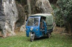 Véhicule de transport à trois roues bleu dans la forêt en pierre images libres de droits