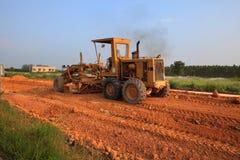 Véhicule lourd de machine de niveleuse travaillant au site de construction de routes Image stock