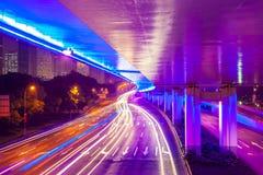 Véhicule mobile avec la lumière de tache floue par la ville la nuit Image libre de droits