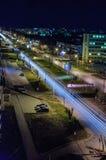 Véhicule mobile avec la lumière de tache floue par la ville la nuit Photographie stock libre de droits