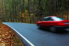 Véhicule rouge sur la petite route Photo libre de droits