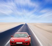 Véhicule rouge sur la route de désert Photos libres de droits